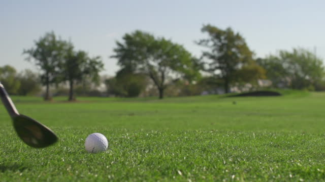 golfer hitting wedge shot in slow motion - golf stock-videos und b-roll-filmmaterial