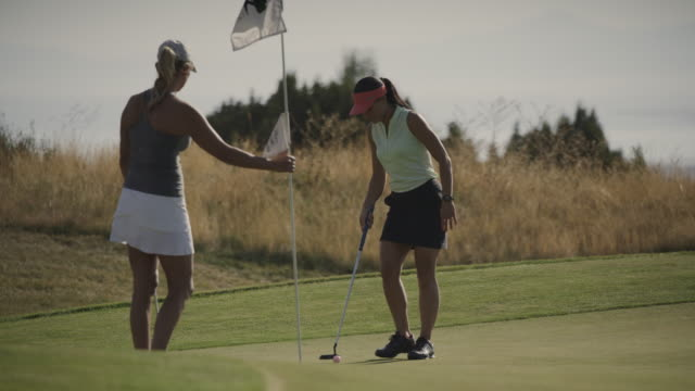 golfer holding flag for woman successfully putting then high-fiving / cedar hills, utah, united states - golf swing stock videos & royalty-free footage