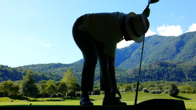 golfer in silhouette hitting the golf ball with driver on driving range - golf swing women stock videos & royalty-free footage