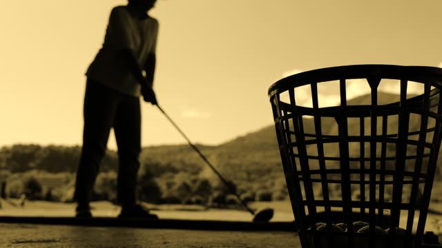 vídeos de stock e filmes b-roll de golfer in silhouette hitting the golf ball with driver on driving range - golf