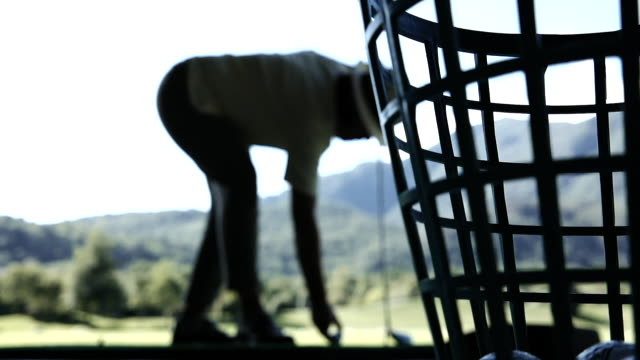 golfer in silhouette hitting the golf ball with iron club on driving range - driving range stock videos & royalty-free footage