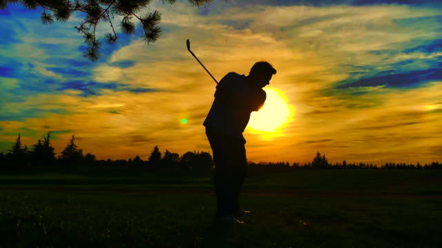 golfer in silhouette with golf swing against sun in sunset - golf swing silhouette stock videos & royalty-free footage