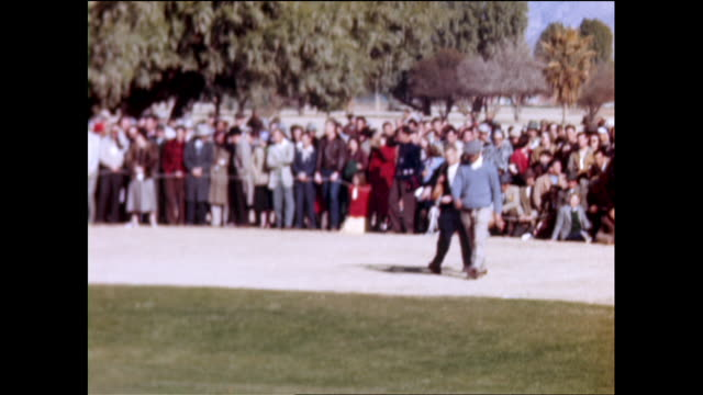 golfer in yellow sweatshirt picking up golf ball as crowd watches behind white rope panning view of crowd gathered behind white rope surrounding the... - sweatshirt stock videos & royalty-free footage