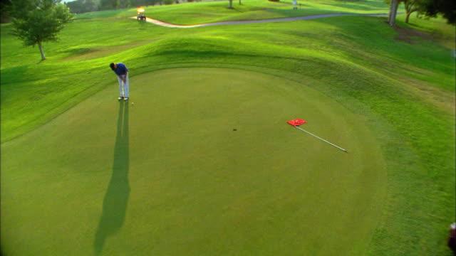 a golfer just misses a putt on a green. - golfgreen bildbanksvideor och videomaterial från bakom kulisserna