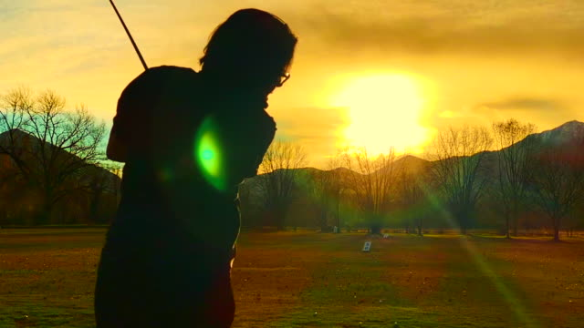 golfer making a golf swing in slow motion against the sun and mountain - ゴルフのスウィング点の映像素材/bロール