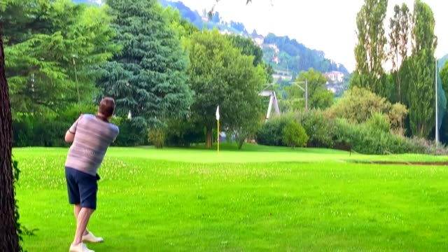 golfer making chipping shot to putting green - putting green stock videos & royalty-free footage