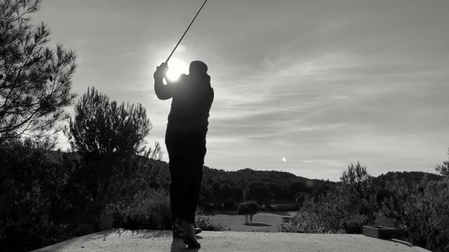 golfer making golf swing against sun - golf swing silhouette stock videos & royalty-free footage