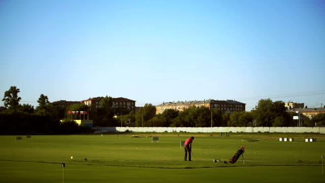 golfer on a green field in urban district - teeing off stock videos & royalty-free footage