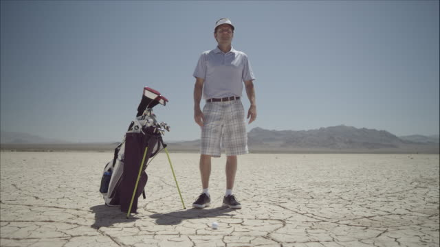 Golfer on dry lakebed looks into distance.