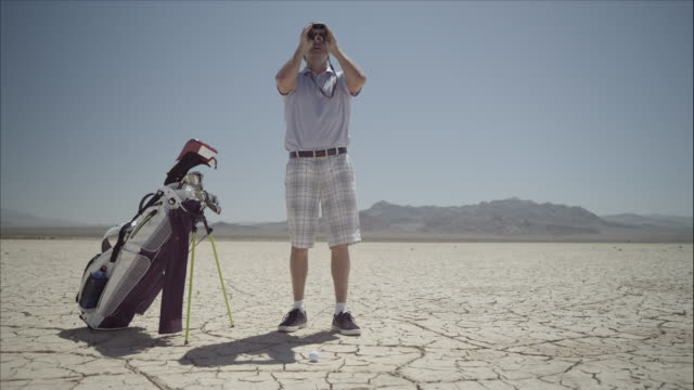 Golfer on dry lakebed uses binoculars to look into distance.