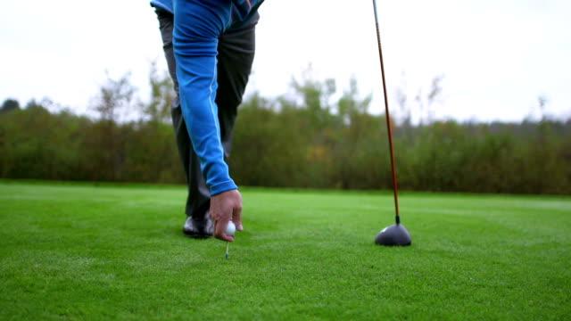 vidéos et rushes de balle de golf sur tee-shirt lieux - tee de golf