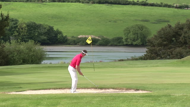 ms, golfer playing golf in bunker, kinsale, ireland - golf swing on white stock videos & royalty-free footage