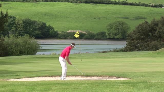 ms, golfer playing golf in bunker, kinsale, ireland - ゴルフのスウィング点の映像素材/bロール