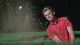A Golfer plays an explosive shot in slow motion from a sand trap.