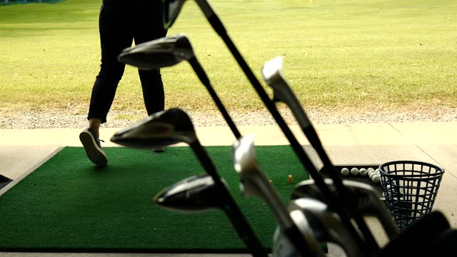 vídeos de stock e filmes b-roll de golfer practice golf swing with her driver in driving range and with a golf bag with golf club - golf