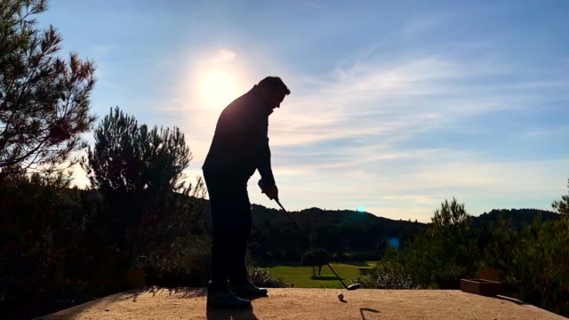 golfer preparing to teeing off  the golf ball against sun - golfer stock videos & royalty-free footage