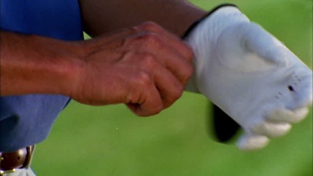 a golfer pulls on a golf glove and grips his club. - golf glove stock videos and b-roll footage