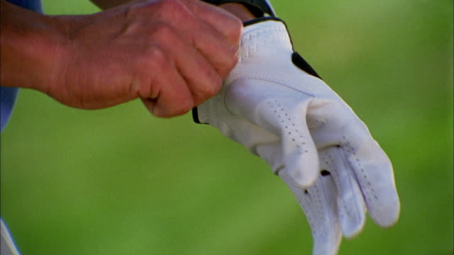 a golfer pulls on a golf glove and grips his club. - golfer stock videos and b-roll footage