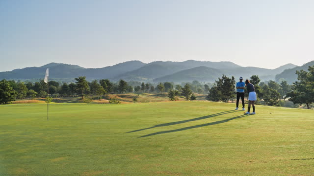vídeos y material grabado en eventos de stock de golfer putt pelota a hoyo en el campo de golf verde, fondo de la escena del cielo. - golf