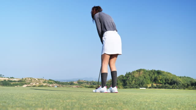 golfer putt ball to hole on green golf course, sky scene background. - putting stock videos & royalty-free footage