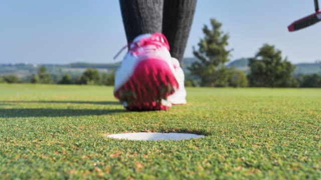 golfer putt ball zu loch auf grünem golfplatz, himmel szene hintergrund. - bunker stock-videos und b-roll-filmmaterial