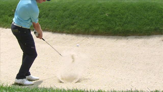 vidéos et rushes de golfer putting ball from trap - ball trap