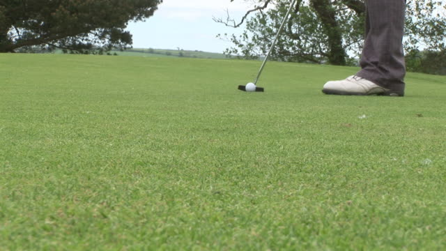 vídeos y material grabado en eventos de stock de cu, golfer putting ball into hole, low section, kinsale, ireland - putt