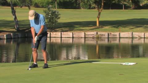 vídeos de stock, filmes e b-roll de golfer putting ball, medium shot, spain - obstáculo de água