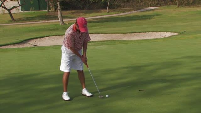 vídeos de stock, filmes e b-roll de golfer putting ball, spain - green de golfe