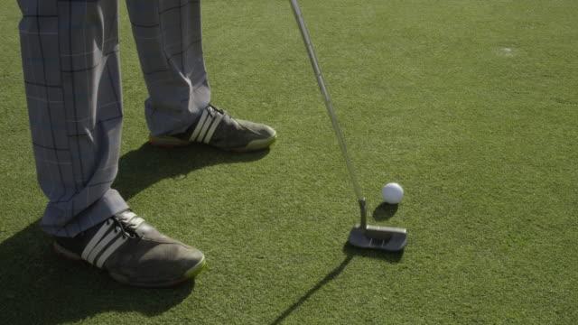 HA TS golfer putting, camera tracks golf ball rolling across green until it drops into hole, RED R3D 4K