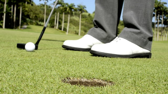 golfer, putting, detail of ball and shoes - hole stock videos and b-roll footage