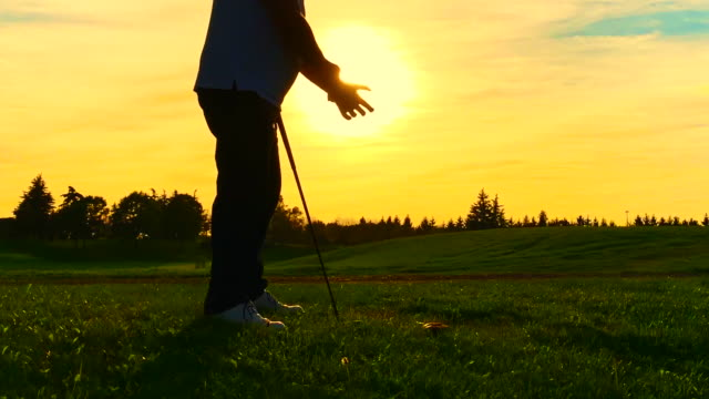 golfer putting on his golf glove against sun in sunset - one man only stock videos & royalty-free footage