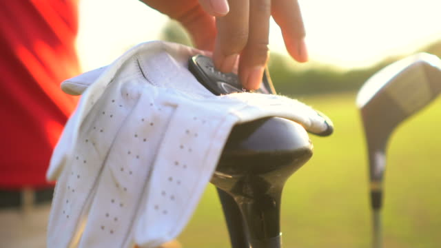golfer putting on white golf gloves - sports glove stock videos & royalty-free footage