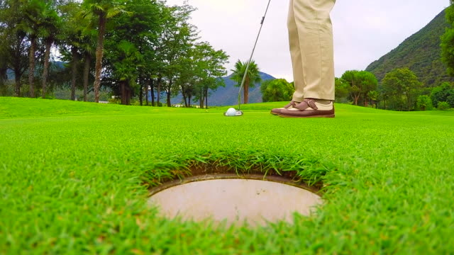 vidéos et rushes de golfer putting the golf ball - tirer