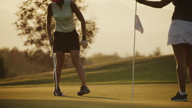 vidéos et rushes de golfer putting then celebrating with friend removing flag at sunset / cedar hills, utah, united states - golf