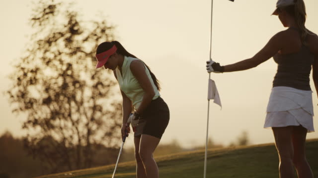 golfer putting then high-fiving with friend removing flag at sunset / cedar hills, utah, united states - putting stock videos & royalty-free footage