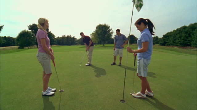 MS, Golfer putting towards hole with colleagues cheering, Seco, Maine, USA