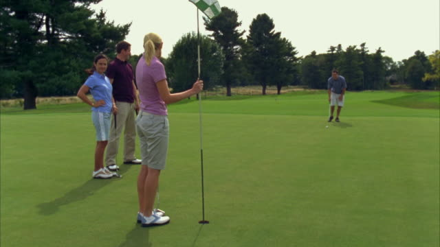 MS, SHAKY, Golfer putting towards hole with colleagues standing around, Seco, Maine, USA