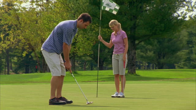 ms, golfer putting towards woman holding flag pole, seco, maine, usa - flagpole stock videos & royalty-free footage