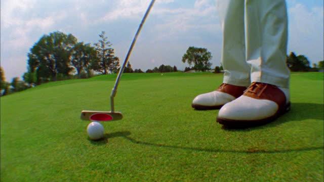 A golfer putts a golf ball.