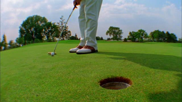 vídeos y material grabado en eventos de stock de a golfer putts and the ball sinks into the cup. - putt