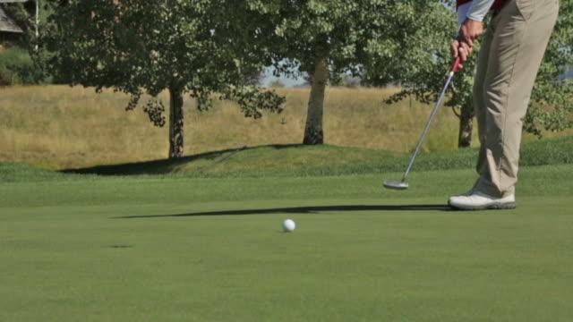 a golfer putts at a golf course in idaho - パットする点の映像素材/bロール