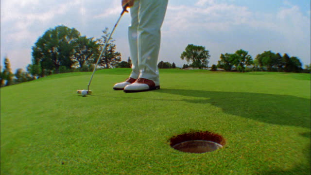 a golfer putts the ball into the hole and then picks it up. - パットする点の映像素材/bロール