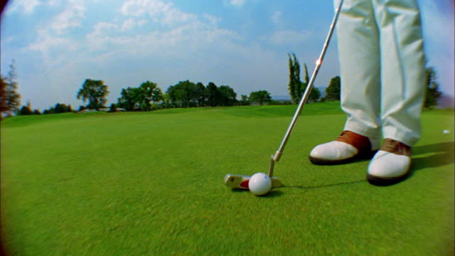 a golfer putts the ball into the hole. - golfplatz green stock-videos und b-roll-filmmaterial