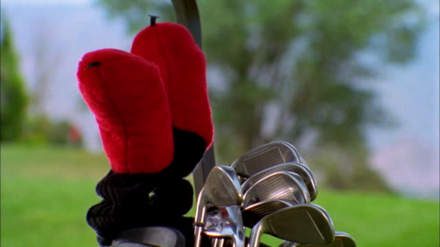 A golfer removes the cover from a golf club.