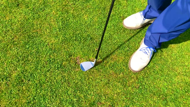 golfer repairing divot with golf club on golf course - golf shoe stock videos & royalty-free footage
