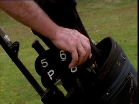 golfer retrieves 7 iron from golf bag, victoria, australia - golf bag stock videos & royalty-free footage