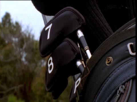 Golfer retrieves 7 iron from golf bag, Victoria, Australia