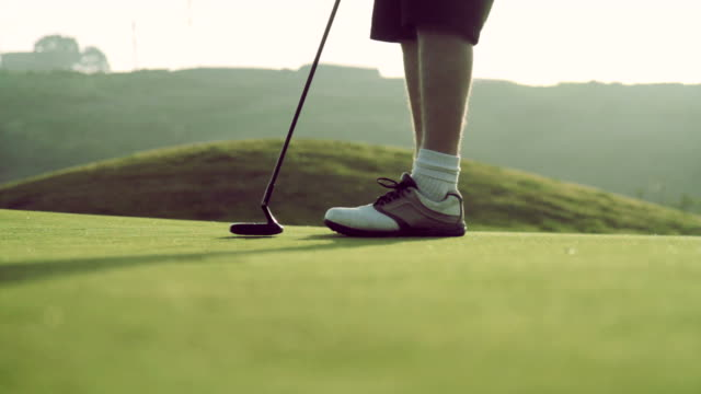 golfer sinks a putt at sunset shot in hd - golf ball stock videos and b-roll footage