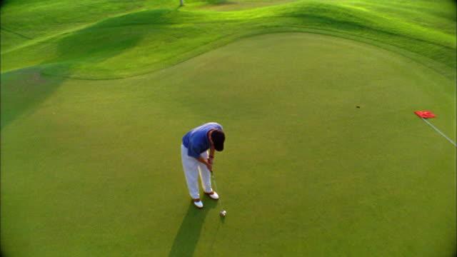 a golfer successfully makes a putt on a green. - einlochen golf stock-videos und b-roll-filmmaterial